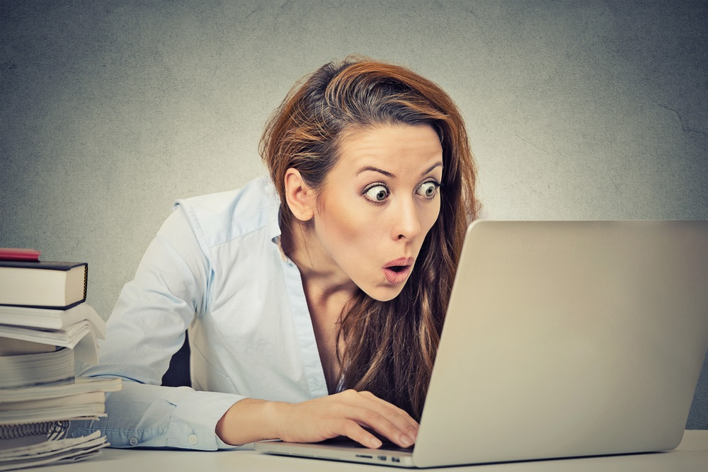 Portrait young shocked business woman sitting in front of laptop computer looking at screen isolated grey wall background. Funny face expression emotion feelings problem perception reaction .jpeg