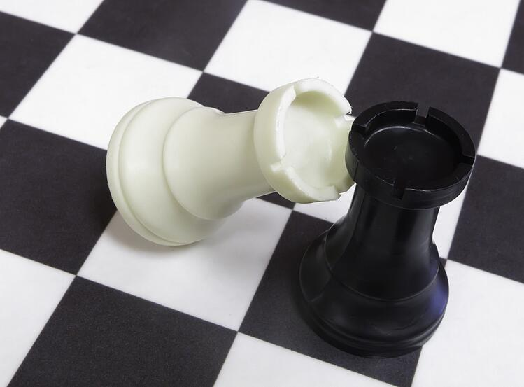 White rook topples against black rook on chessboard.jpeg