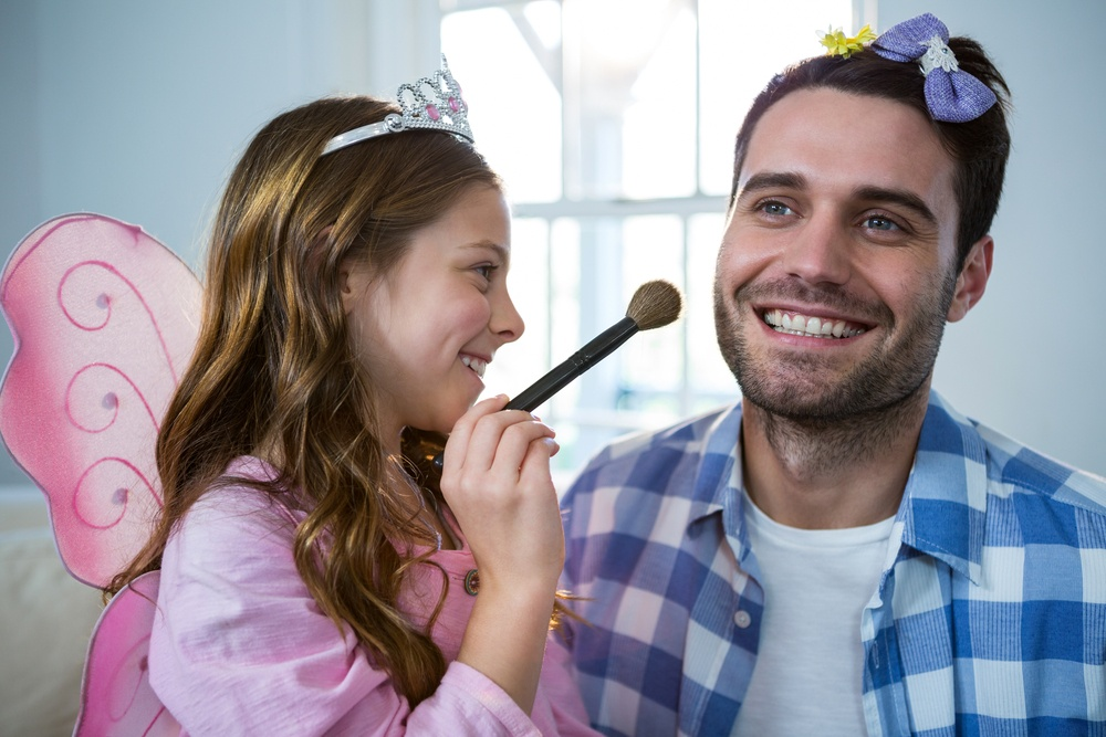 Girl dressed up in a fairy costume applying make-up on fathers face at home