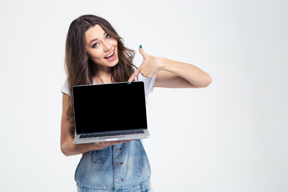 Portrait of a cheerful girl showing blank laptop computer screen isolated on a white background